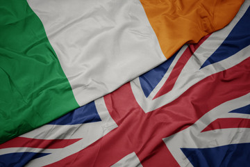 Wall Murals Northern Europe waving colorful flag of great britain and national flag of ireland.