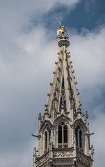 Brussels, Belgium - June 22, 2019: Closeup of gray stone spire of city hall on Grand Place against blue sky with white clouds. Golden Saint Michael statue on top.