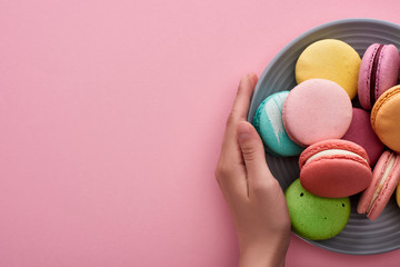 cropped view of woman holding plate with multicolored delicious French macaroons on pink background with copy space
