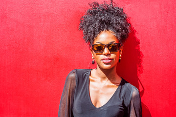 Portrait of Young African American Woman in New York City. Young black woman with afro hairstyle wearing long sleeve mesh sheer shirt, sunglasses, standing against red background under sun..
