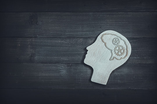 Human head and face with gear sign  on wood table background. Brain of thinking about driving the organization , Symbol of Process and Positive Mind concept