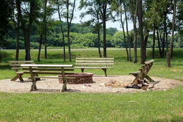The empty benches around the fire pit in the countryside.