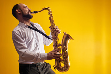 Portrait of professional musician saxophonist man in  white shirt plays jazz music on saxophone, yellow background in a photo studio, side view Fotobehang