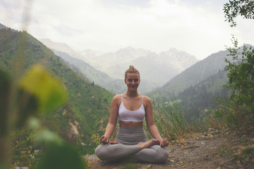 Deurstickers Ontspanning Sport girl doing yoga in mountains beautiful landscape. Young woman leads healthy lifestyle, meditates, relaxes lotus position in bright sportswear on nature