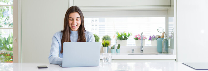 Wide angle picture of beautiful young woman working or studying using laptop with a happy face standing and smiling with a confident smile showing teeth