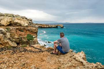 man sits on the edge of a cliff and looks into the distance at sea