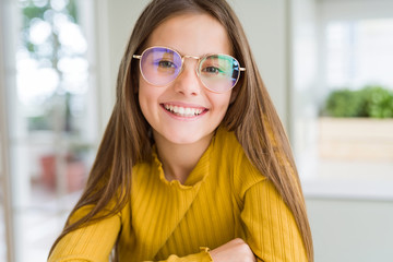 Beautiful young girl kid wearing glasses smiling looking side and staring away thinking.