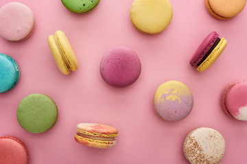 pattern of multicolored delicious French macaroons scattered on pink background Wall mural