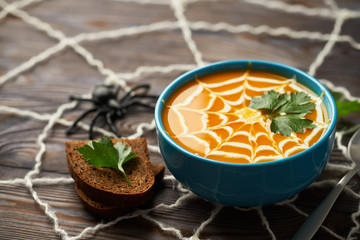 A healthy pumpkin puree garnished with cream and parsley leaves. Composition autumn cream soup with toys for the holiday Halloween on a dark wooden background