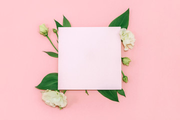 Paper blank with fresh white flowers on pastel pink background. Flat lay, top view.