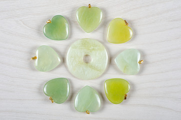 Minimalistic still life of butter jade donut with six hearts stone different tones.