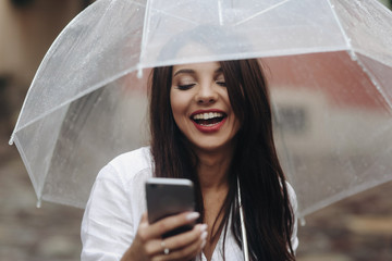 Close up portrait of smiling beautiful girl with umbrella, using smartphone, red wall on the background. Small depth of field. It's summer rain.