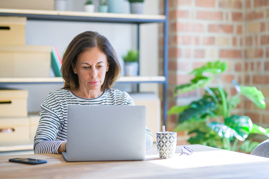 Middle age senior woman sitting at the table at home working using computer laptop with a confident expression on smart face thinking serious