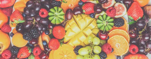 Wall Mural - Healthy fruit platter background, strawberries raspberries oranges plums apples kiwis grapes blueberries mango persimmon, top view, selective focus. Long photo banner, toned