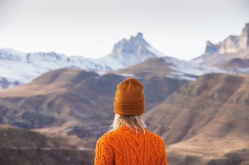 Portrait from the back of the girl traveler in an orange sweater and hat in the mountains against the background of a frozen mountain. Photo travel concept Wall mural