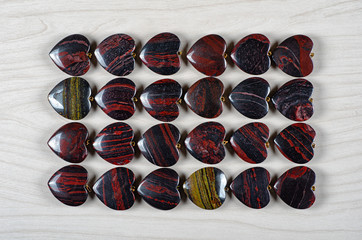 Four rows of red and iron tiger eye heart-shaped stones on white wooden background