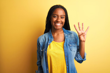 Young african american woman wearing denim shirt standing over isolated yellow background showing...