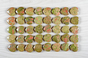 Forty unakite heart-shaped stones as background