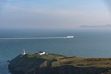 Cruise ship passing by lighthouse close to Howth Summit, Dublin, Ireland