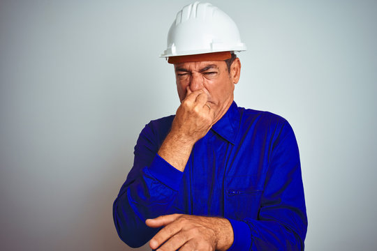 Handsome middle age worker man wearing uniform and helmet over isolated white background smelling something stinky and disgusting, intolerable smell, holding breath with fingers on nose. Bad smells