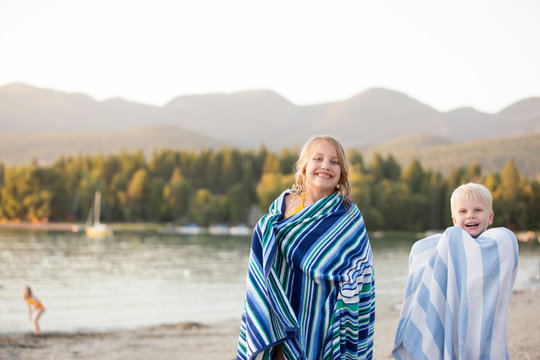 Young boy and girl wrapped in beach towels after swimming in Whitefish Lake