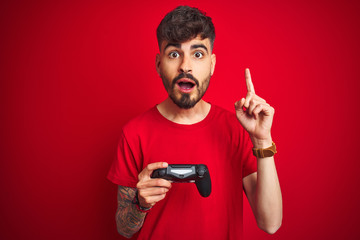 Young gamer man with tattoo playing video game standing over isolated red background surprised with an idea or question pointing finger with happy face, number one