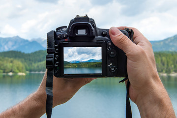 Hands of a male photographer holding a digital camera taking pictures of a idyllic landscape with a lake and mountains while the picture shows at the display