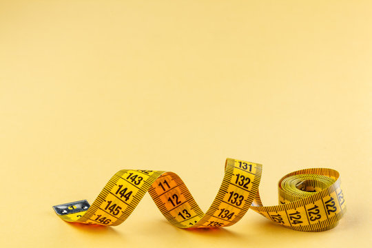 Yellow measuring tape on yellow background. Measuring tape for fitness. Close up