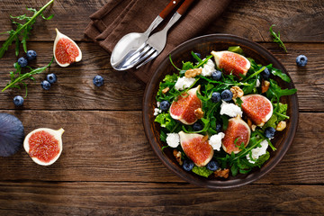 Fig salad with goat cheese, blueberry, walnuts and arugula on wooden background. Healthy food. Top view Wall mural