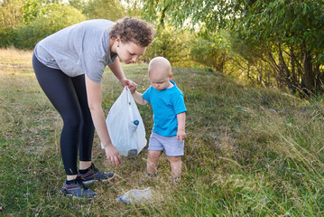 Mom teaches her son to clean up trash in nature. The topic of environmental pollution by garbage.