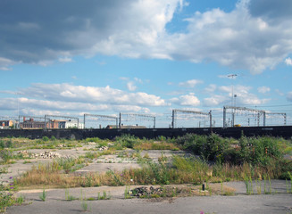 a large unused urban brownfield site with open land covered in cracked overgrown concrete awaiting development in leeds england