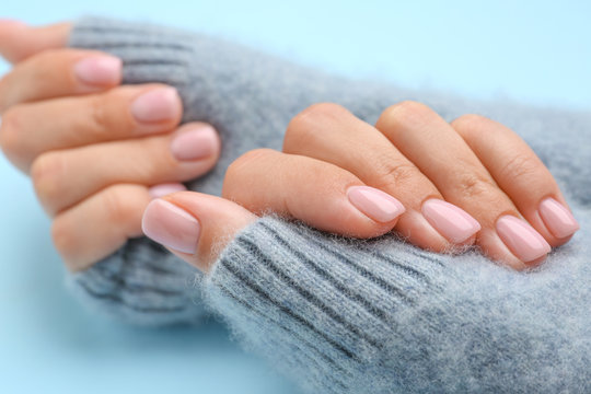 Hands of woman with beautiful manicure on color background, closeup