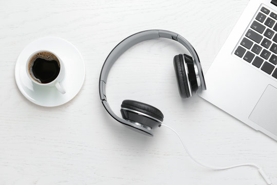 Modern headphones, laptop and cup of coffee on white background