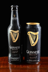 IRVINE, CA - JUNE 18, 2015: A bottle and can of Guinness Draught on a wet bar. Guinness producing beer in Ireland since 1759, is one of the most successful brands in the world.