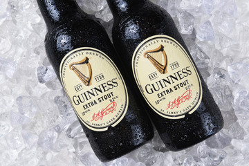 IRVINE, CA - December 15, 2017: Two bottles of Guinness Extra Stout on a bed of ice. The Irish beer is one of the worlds most successful beer brands with annual sales over 850 million liters.