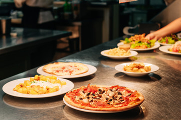 Food orders on the kitchen table in the restaurant, pizza with ham and mushrooms champignons, potatoes with garlic sauce, flammkuchen Wall mural