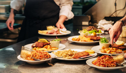 Food orders on the kitchen table in the restaurant, pasta spaghetti with tomato sauce and cheese, schnitzel with spaetzle