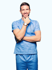 Handsome doctor man wearing medical uniform over isolated background looking confident at the camera with smile with crossed arms and hand raised on chin. Thinking positive.