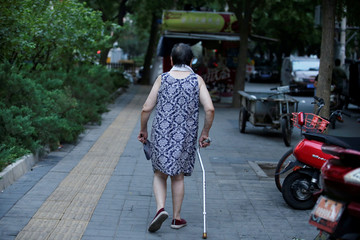 An elderly woman walks with a stick along a street in downtown Beijing