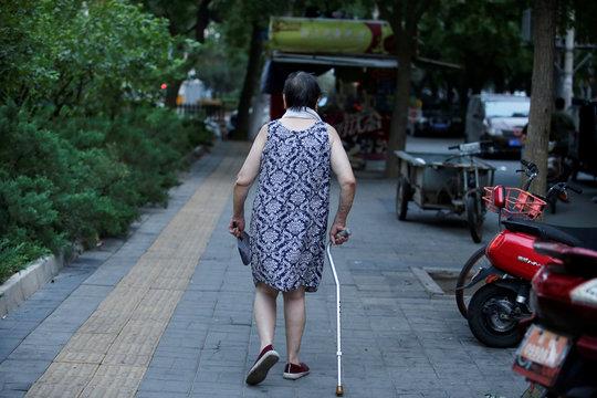 An elderly woman walks with a stick along a street in downtown Beijing