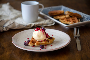 Close up of delicious crunchy waffle with ice cream and berries with coffee and more waffles in the background, wooden table setting