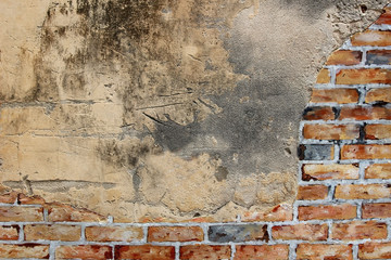 Abstract background of an old wall with half brick pattern and the rest exposed concrete.
