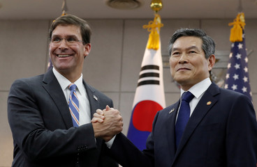 U.S. Defense Secretary Mark Esper and South Korean Defense Minister Jeong Kyeong-doo hold their hands ahead of a meeting at Defense Ministry in Seoul