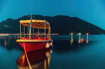 Long exposure teal and orange sunset view of Kotor Bay and a docked boat in postcard perfect town of Perast Montenegro