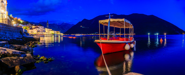 Sunset panoramic view of Kotor Bay and a docked boat in the postcard perfect town of Perast, Montenegro, long exposure
