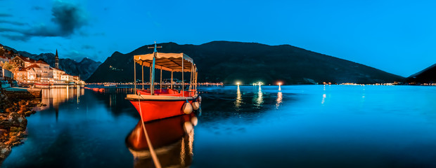 Kotor Bay, long exposure teal and orange sunset panorama and a docked boat in postcard perfect town of Perast Montenegro