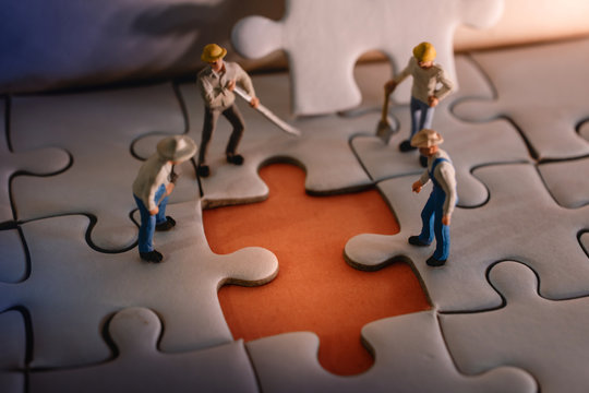 Teamwork and Solving Problem Concept. Group of Miniature Worker Men Found Something Wrong on the Work Process (a Piece of Jigsaw Puzzle)