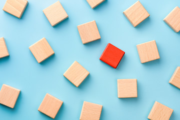 Red wooden block standing out from the group wooden blocks on blue background. Leadership, dissenting opinion, divergent views concepts