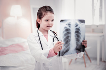 Cheerful cute girl learning how to be a doctor