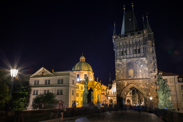 People at the Charles Bridge (Karluv most) and lit St. Francis of Assissi Church and Old Town Bridge Tower at the Old Town in Prague, Czech Republic, in the evening.